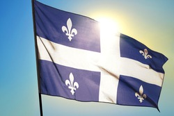 Quebec province of Canada flag waving on the wind in front of sun