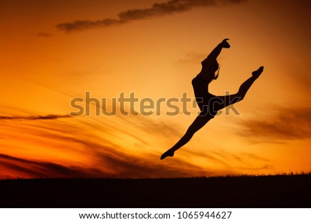 QUEBEC, QC - CANADA AUGUST 2011 : The silhouette of a ballerina jump in front of an orange sunset sky. She feels free as a bird. #1065944627