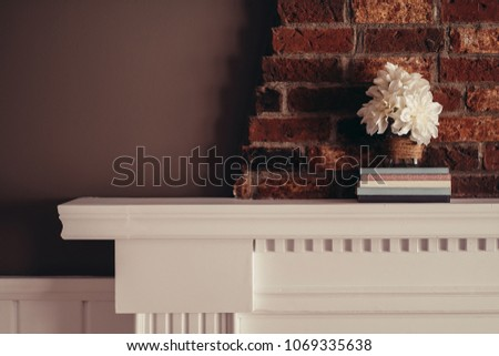 QUEBEC, QC - CANADA FEBRUARY 2017 : A fake flowers arrangement in a mason jar glass over five outmatching books. The jar has jute twine rolled around it and the setup takes place on a fireplace mantle