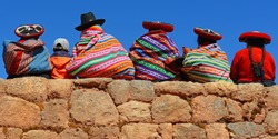 Quechua ladies and a young boy chatting on an ancient Inca wall.