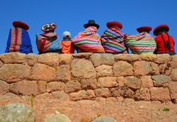 Quechua ladies and a young boy chatting on an ancient Inca wall, Cusco Province, Peru.
