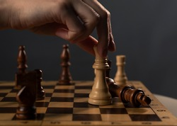 Queen beating king on chessboard. Checkmate in chess. Female hands and dark gray background.
