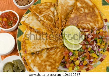 Quesadilla - Mexican Spicy Chicken Tinga Quesadillas served with sour cream, refried beans, salsa, jalapenos and lime wedges