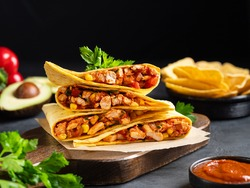 Quesadillas with chicken breast, corn, red pepper, tomatoes and sauce stacked on wooden cutting board. Traditional toasted sandwich, mexican snack, corn tortilla wraps and nachos. Black background.