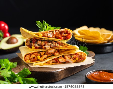 Quesadillas with chicken breast, corn, red pepper, tomatoes and sauce stacked on wooden cutting board. Traditional toasted sandwich, mexican snack, corn tortilla wraps and nachos. Black background. Foto stock ©
