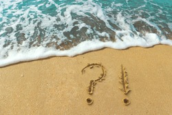 question and exclamation marks are drawn on the golden sand of the beach. The azure wave on the ocean shore. The concept of actual issues and problems of recreation, sea, tourism.