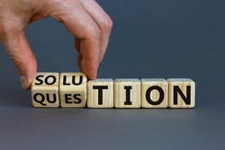 Question and solution symbol. Businessman turns wooden cubes and changes the word 'question' to 'solution'. Beautiful grey table, grey background, copy space. Business, question and solution concept.