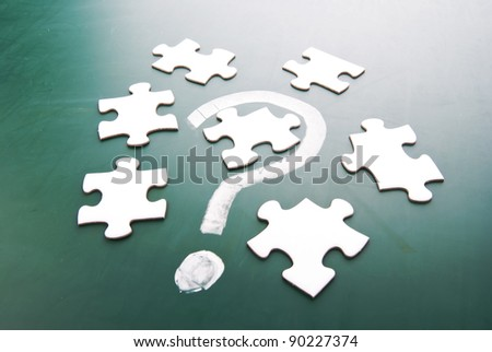Question mark and puzzle pieces on blackboard