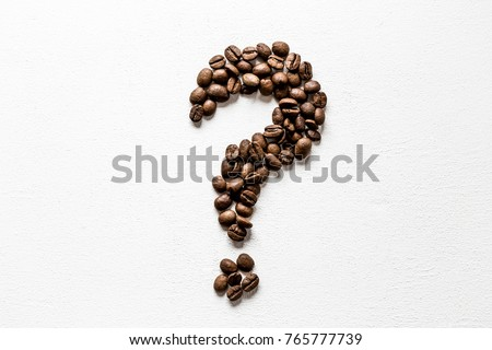 Question mark created from brown beans on the white table. Harvest of coffee in different countries. Choice of the best sort and quality coffee. Empty place for a text. #765777739