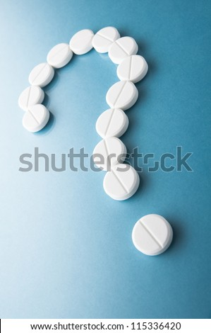 Question mark  from pills  on blue background