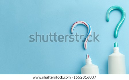 Question mark from toothpaste. Concept of choosing good toothpaste for teeth whitening. Tube of colored toothpaste on blue background. Copy space for text Foto stock ©