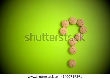 Question mark made by brown pills on green background. Creative medical health, medical problems, medication interactions, medication errors and pharmaceutical concept. #1400719391