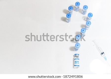 Question mark made from bottles of coronavirus vaccines and on the white, a syringe near, top view. Concept of uncertainty and risks when using new covid vaccines