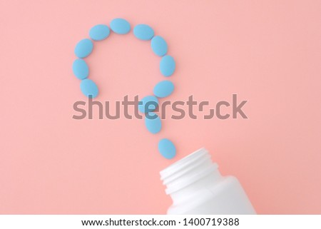 Question mark of blue pills on pink background of empty white jar. Creative medical health, medical problems, drug interactions, drug errors and pharmaceutical concept. #1400719388