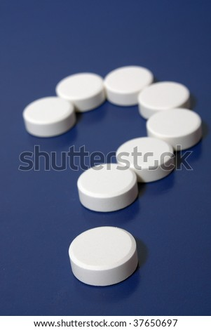 Question mark of white tablets on dark blue background.