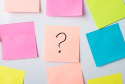 Question mark on a sticky note on a board. Concept of question, uncertainty, asking, inquiry, interrogation