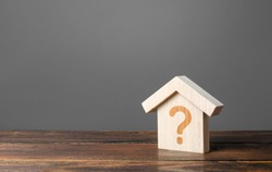 Question mark on a wooden house. Cost estimate. Solving housing problems, deciding to buy or rent real estate. Search for options, choice of type of residential buildings. Property valuation