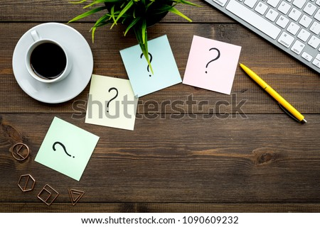 Question mark on sticky notes on office desk on dark wooden background top view copy space. FAQ concept. Working with clients. Troubles in work.