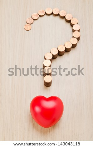 Question mark sign made out of coins and red heart