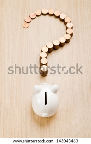Question mark sign made out of coins in front of a piggy bank