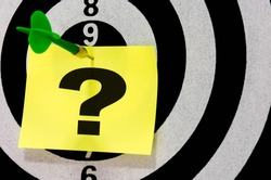 Question mark symbol on dart arrow hitting background. Dart board game target of Questions and Answers on paper.