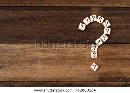 question mark tiles arranged forming bigger question mark. question mark on wooden table background
