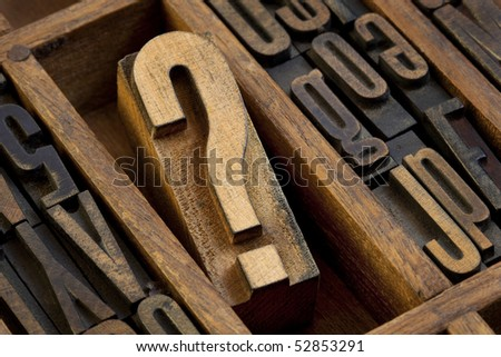 question mark - vintage wooden letterpress type block in old typesetter drawer among other letters stained by ink - stock photo