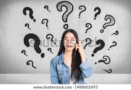 Question Marks with young woman in a thoughtful pose.Asianl woman with questioning expression and question marks above her head.Hand draw sketch question icon.