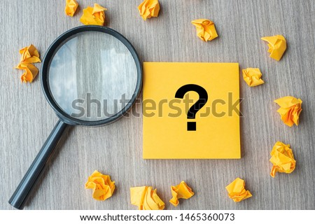Questions Mark ( ? ) word on yellow note with crumbled paper and magnifying glass on table background. Idea, Analysis, Keyword, Content, SEO,FAQ, Answer, Q&A and Information concept