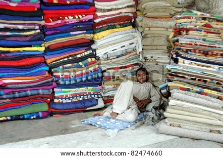 QUETTA, PAKISTAN - AUG 08: A shopkeeper takes nap at his shop during the Holy Month of  Ramazan-ul-Mubarak on August 08, 2011 in Quetta.