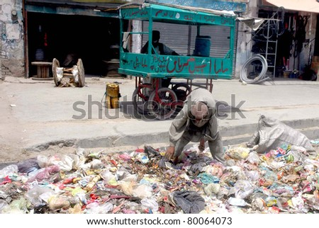 QUETTA, PAKISTAN - JUN 27: A man who collects garbage to earn his livelihood to support his family searches useful items at a heap of garbage that lays down at street on June 27, 2011in Quetta, Pakistan.