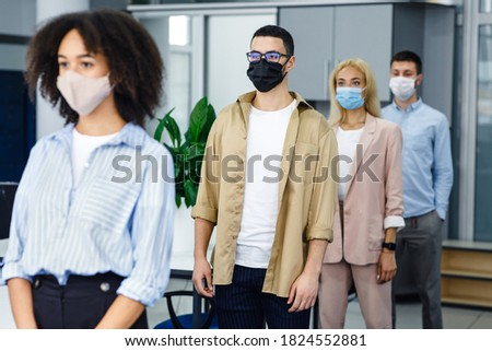 Queue to check temperature before work and new normal after lockdown and social distancing. Multiracial workers in protective masks near office entrance on job during coronavirus epidemic