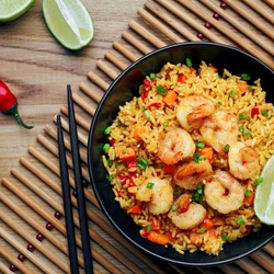 Quick and healthy Asian meal made of fried rice, fresh shrimps, lime and vegetables in a black bowl on a wooden table. Top view, directly above shot.