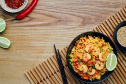 Quick and healthy Asian meal made of fried rice, fresh shrimps, lime and vegetables in a black bowl on a wooden table. Top view, directly above shot with space for text.