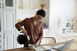 Quick tea break. Smiling indian female freelance worker take pause in online work at home office to make cup of coffee. Young biracial woman brew tea in mug pour hot water from modern electric kettle