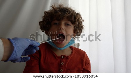 Quick test for suspected coronavirus diagnosis. Doctor taking a nasofaringeal sample of a young boy, with a cotton swab. Covid19 screening. Child Photo stock ©