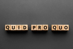 Quid pro quo - words from wooden blocks with letters,