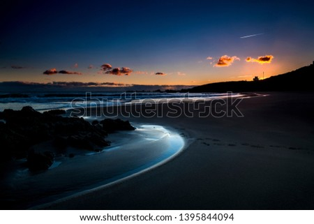 Quiet and relaxed scenic beach place during dusk sunset with coloured sky in background - sea shore outdoor vacation concept - freedom and lifestyle night picture with nobody there