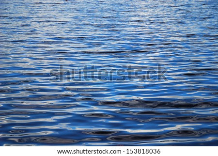 Quiet blue water with waving surface is photographed with diminishing perspective.