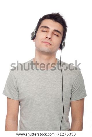 quiet casual young man listening music on headphones (isolated on white background)