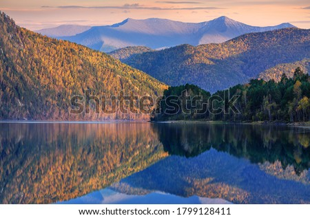 Photo of  Quiet evening on the Yenisei River in the mountains of Siberia. Calm river flow, beautiful reflection. Sunset light.