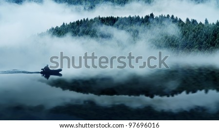 Quiet mountain lake in a thick fog. In the background a mountain forest. Floats on the water in the boat people. The blue tone.