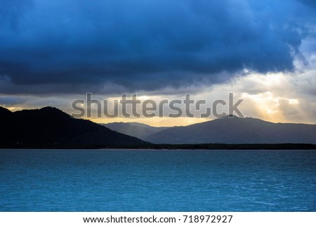Shutterstock Quiet sea with mountains in the background and crepuscular sun rays shining through the clouds. Landscape of Australia