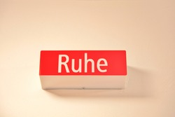 Quiet sign - word Ruhe. sign light box. angle view of icon information lamp, light with the text Ruhe. geman language word - RUHE - Quiet - Wall sign over a entry of a meetingroom