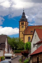 quiet street of an old german town on a sunny day. old church on the background of clouds
