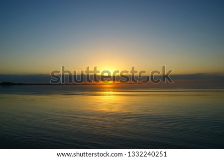 """quiet water of the Caribbean sea. dawn landscape and the first rays of the sun in the dawning sky. """"bay of pigs"""". Playa Larga. Cuba #1332240251"""