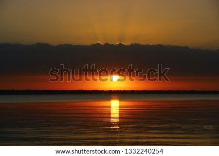 """quiet water of the Caribbean sea. dawn landscape and the first rays of the sun in the dawning sky. """"bay of pigs"""". Playa Larga. Cuba #1332240254"""