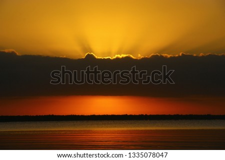 """quiet water of the Caribbean sea. dawn landscape and the first rays of the sun in the dawning sky. """"bay of pigs"""". Playa Larga. Cuba #1335078047"""