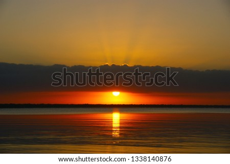"""quiet water of the Caribbean sea. dawn landscape and the first rays of the sun in the dawning sky. """"bay of pigs"""". Playa Larga. Cuba #1338140876"""