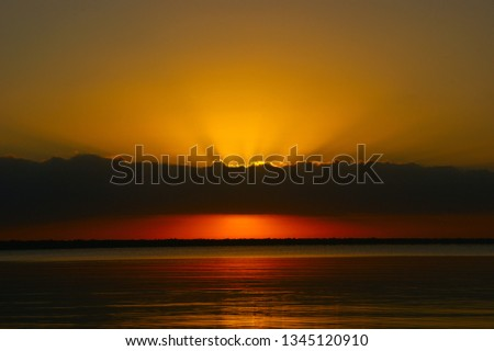 """quiet water of the Caribbean sea. dawn landscape and the first rays of the sun in the dawning sky. """"bay of pigs"""". Playa Larga. Cuba #1345120910"""